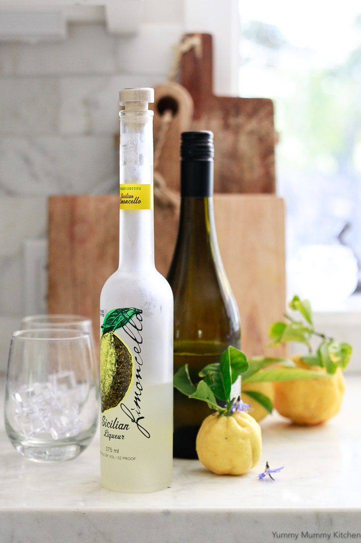 Bottles of limoncello and prosecco sit on a white kitchen countertop with freshly picked lemons.