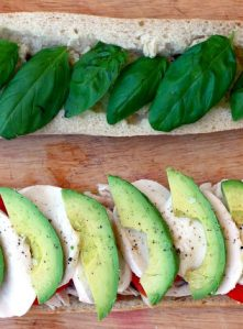 A Caprese sandwich on baguette with avocado, tomato, mozzarella, and basil.