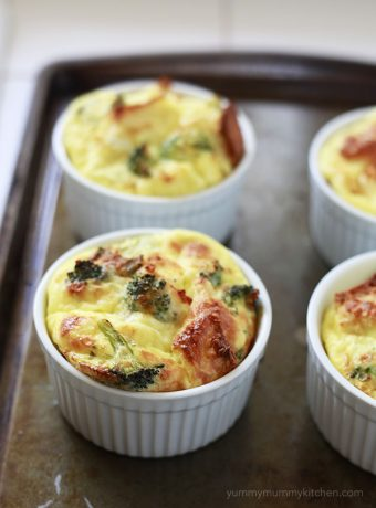 Vegetarian baked egg casseroles in ramekins with broccoli.