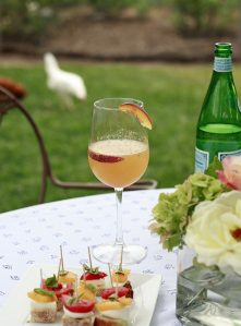 A peach bellini cocktail on an outdoor table next to caprese bruschetta appetizers.