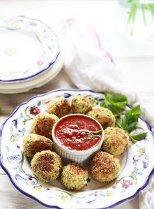Baked arancini rice balls with marinara dipping sauce.