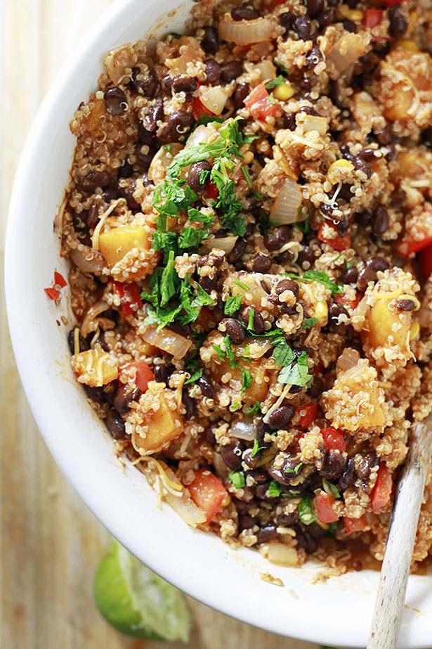 The filling mixture for a quinoa enchilada bake casserole is mixed together in a white bowl. Black beans, quinoa, cheese, butternut squash, and fresh herbs can be seen.
