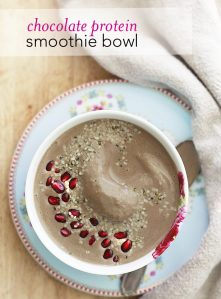 A creamy chocolate smoothie bowl topped with pomegranate seeds and hemp seeds.