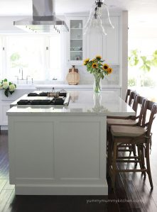 A clean white kitchen with a marble island and wooden barstools.