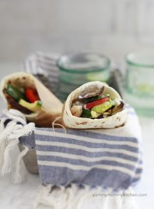 Two vegetarian or vegan gyros with flatbread and grilled vegetables.