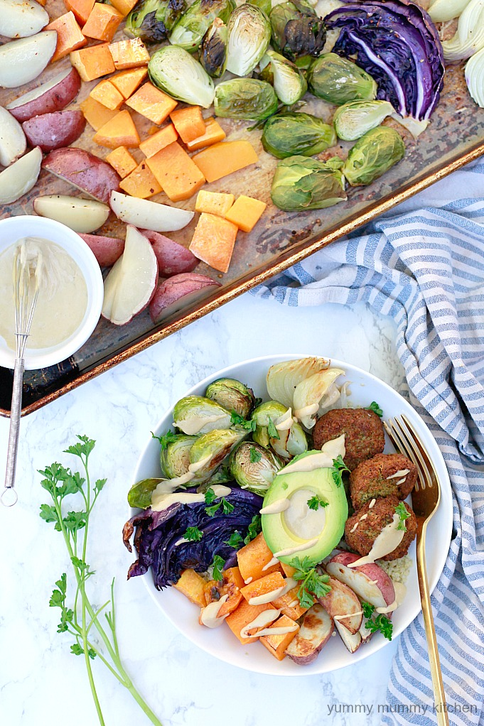 Colorful sheet pan roasted vegetables top a bed of quinoa with falafel, avocado, and tahini sauce for a beautiful Buddha bowl.