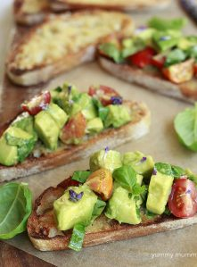 Beautiful and delicious avocado bruschetta with cubed avocado, fresh tomatoes, basil, and white balsamic.