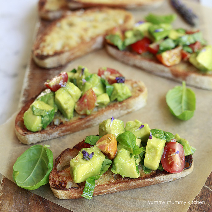 Bruschetta with avocado, tomato, and fresh basil make a tasty snack. It's like a cross between avocado toast and bruschetta!