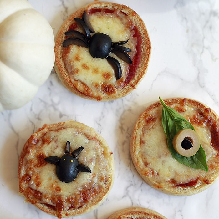 Cute Halloween pizzas made with English muffins and veggies.