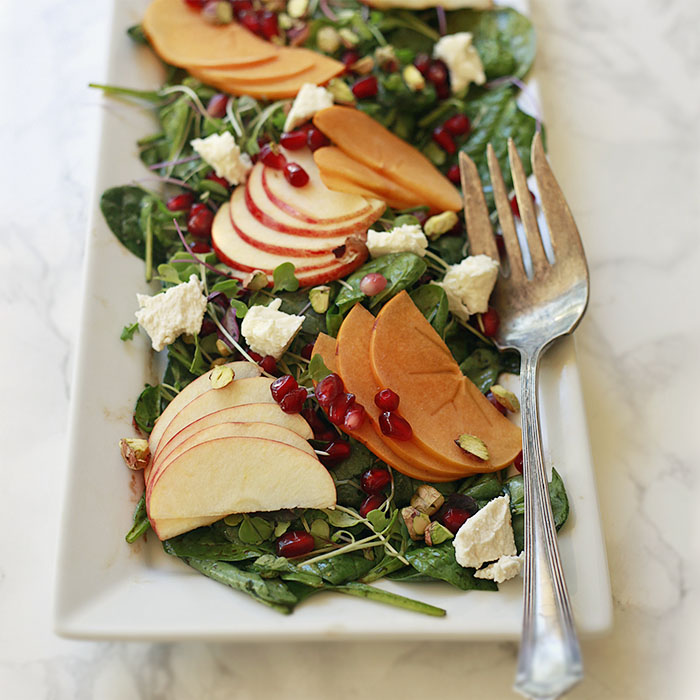 A delightful autumn salad with baby spinach, persimmons, apples, pepitas, and pomegranate. The perfect balance of sweet, salty, creamy and crunchy.