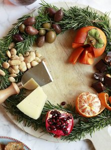 Beautiful wreath cheese board with marcona almonds, chocolate, citrus, pomegranate.