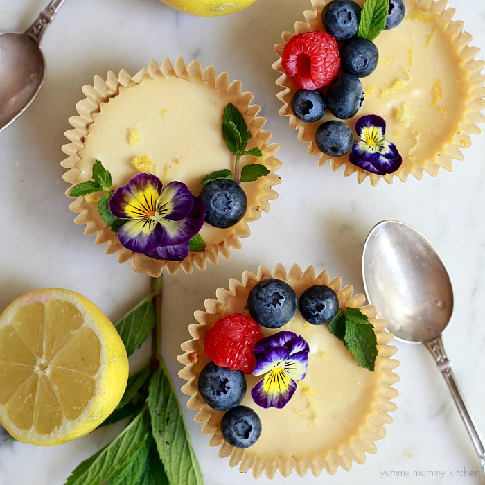 Beautiful and delicious lemon tartlets with almond coconut crusts and fresh berry garnish.