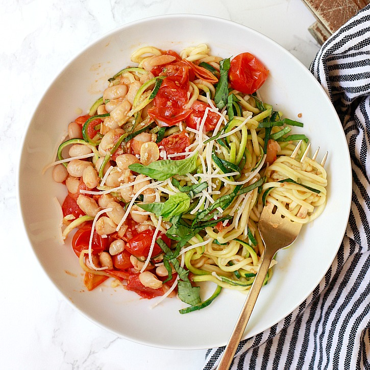 One pan zucchini noodles with roasted cherry tomatoes and white beans is a flavorful and easy meal. It's on the table in under 30 minutes.