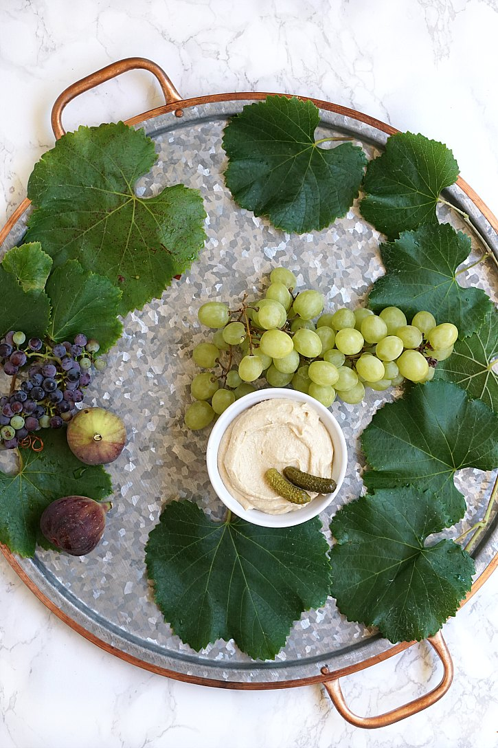 A round Pottery Barn serving tray gets filled with fresh ingredients for a snack platter.