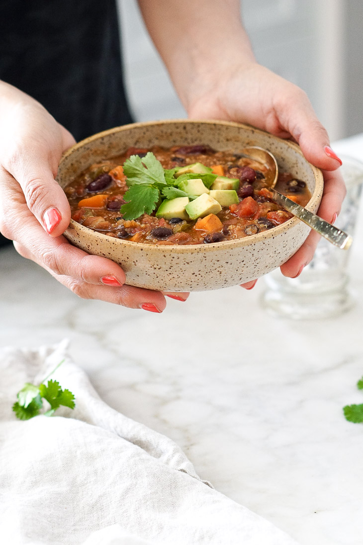 Hands holding a bowl of vegan chili topped with avocado and cilantro. This easy vegetarian chili is made in the Instant Pot or slow cooker.