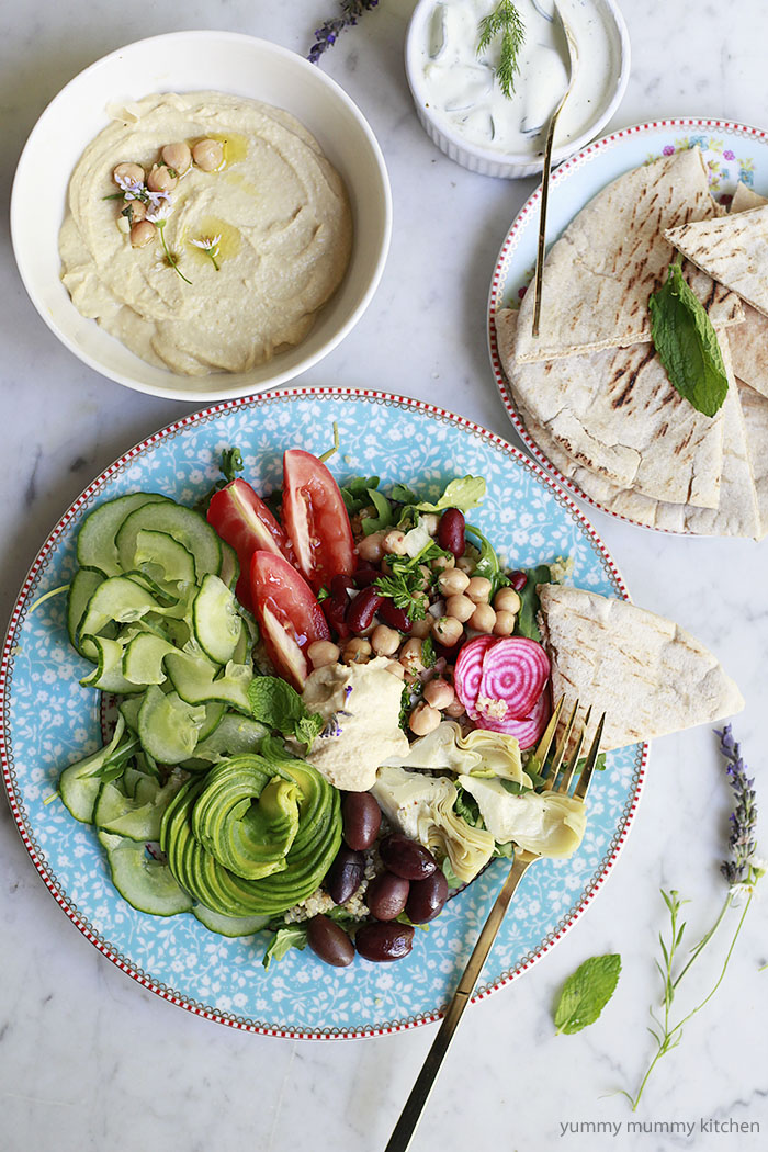 Vegan greek bowls with chickpea salad, cucumber, hummus, flatbread, and olives.