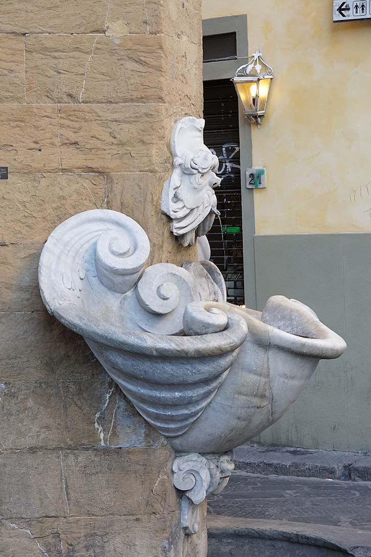 An old marble fountain in the Oltrarno district of Florence Italy