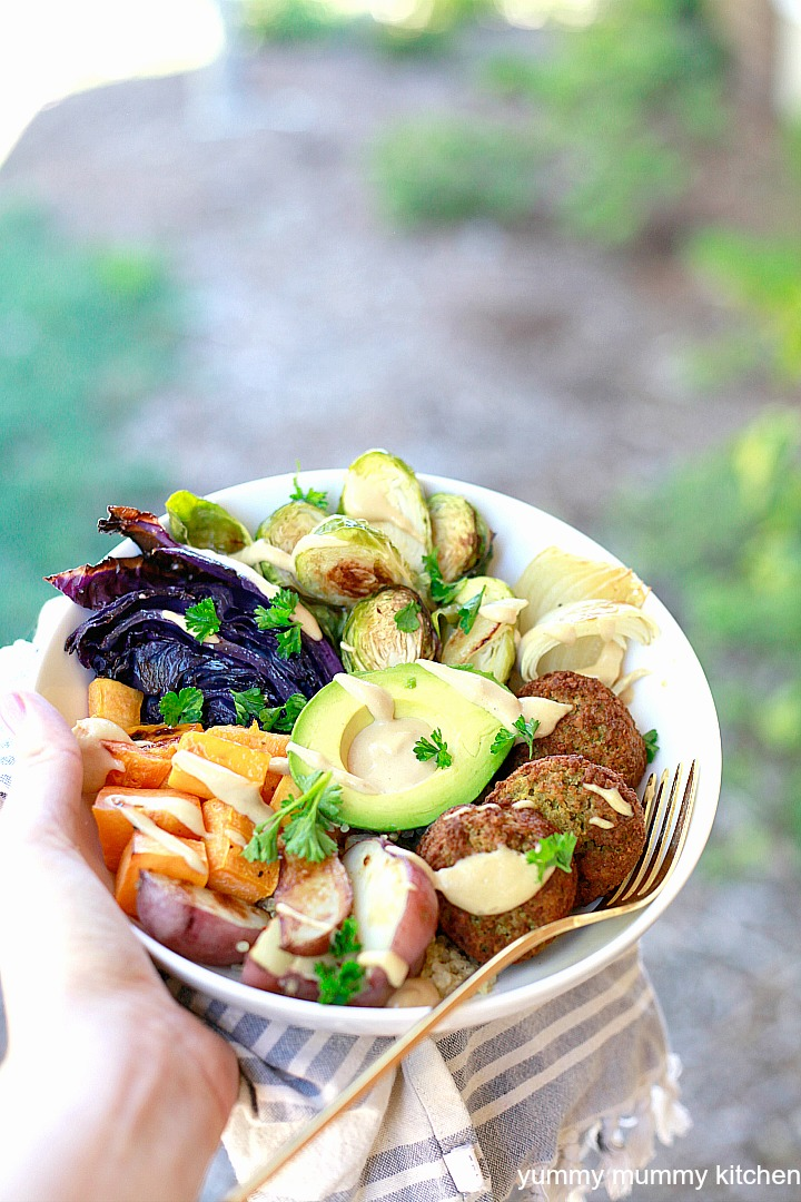 Falafel as part of a Buddha bowl filled with quinoa, vegetables, avocado, and tahini sauce.