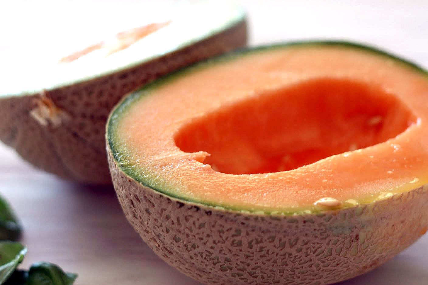 Cantaloupe is halved and seeds scooped out to make melon and prosciutto salad.