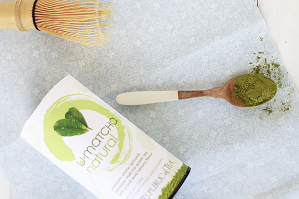 Matcha powder in a spoon with a matcha whisk for making a matcha latte.
