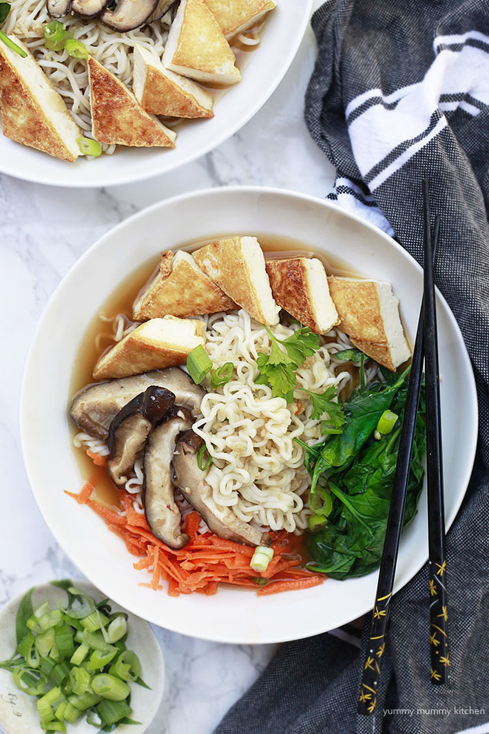 A bowl of vegan ramen noodles and vegetables with crispy tofu triangles.