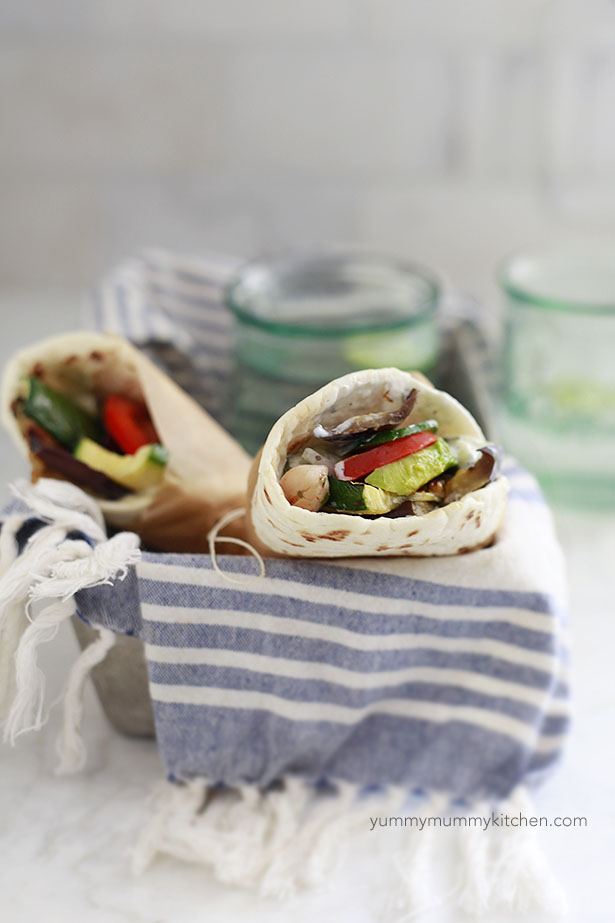 Two vegetarian gyros with vegetables and chickpeas in a basket.