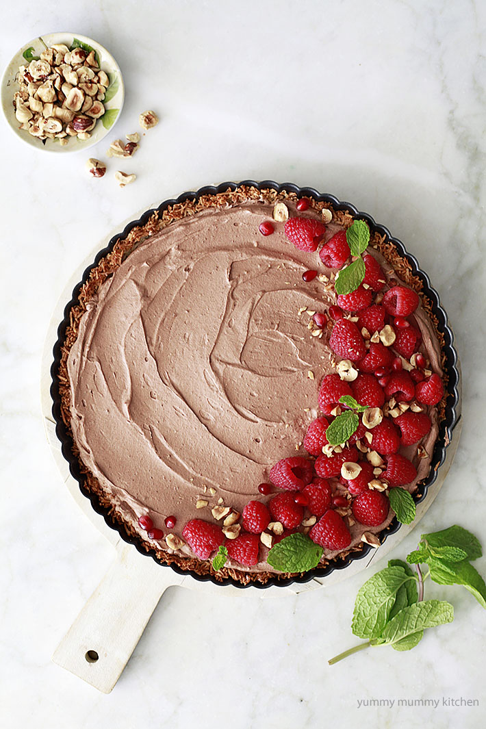 Vegan coconut chocolate mousse pie with coconut crust, raspberries, and hazelnuts.