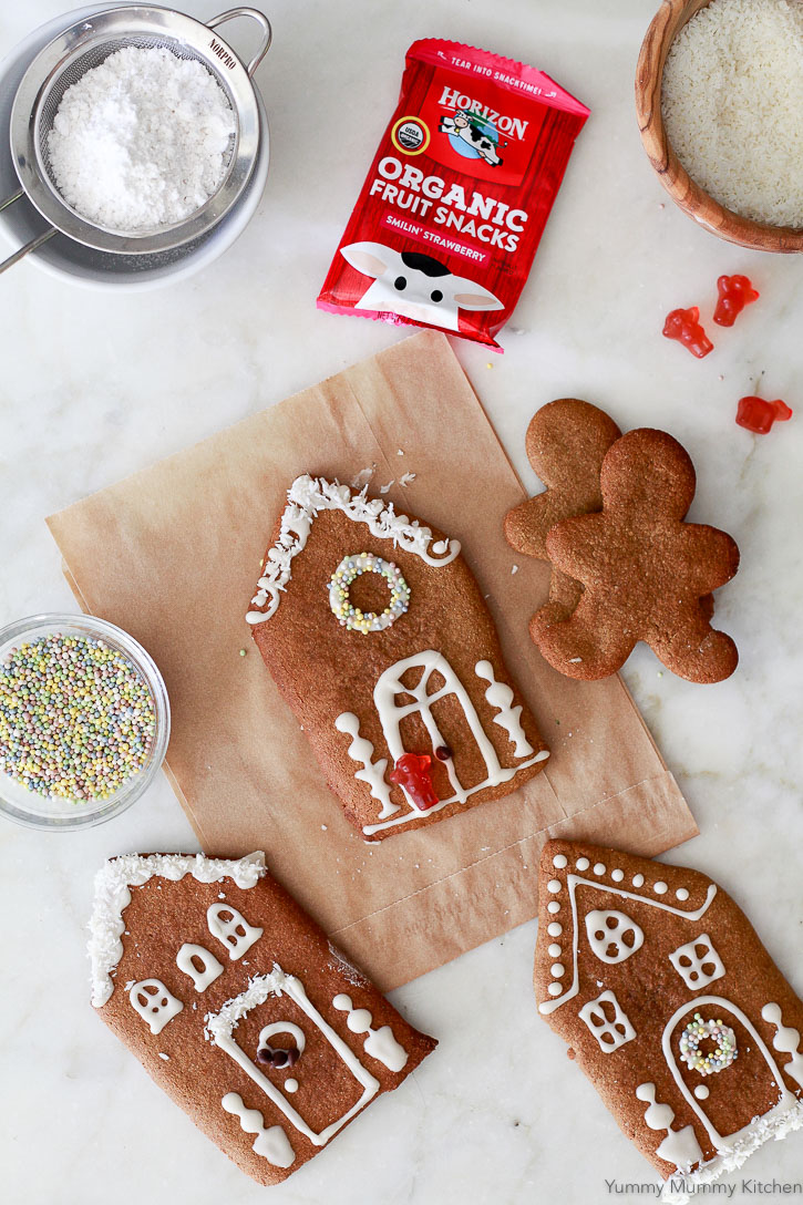 These natural gingerbread house cookies got decorated with dye-free ingredients like sprinkles, fruit snacks, and coconut.