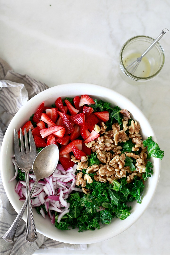 Kale salad with an easy apple cider vinegar, maple, and Dijon dressing. This salad bowl is topped with strawberries, onions, and nuts.