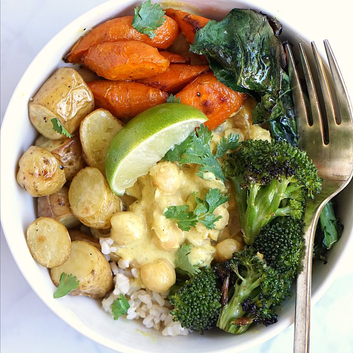 Coconut chickpea curry bowl with rice, broccoli, carrots, and potatoes.