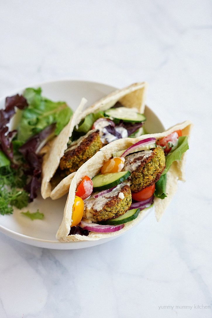 Falafel recipe served in a pita pocket with veggies and tahini sauce.