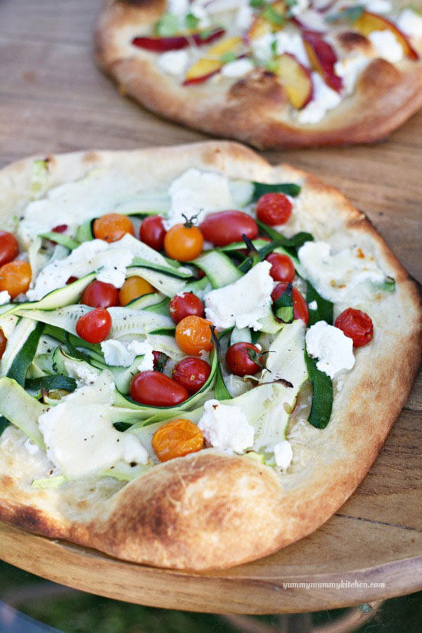 This beautiful and delicious veggie pizza just screams summer! Topped with cherry tomatoes and zucchini ribbons, this fresh pizza doesn't have any sauce.