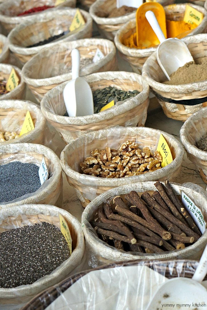 Baskets of seeds, nuts, and spices at a farmers market in Tuscany Italy.