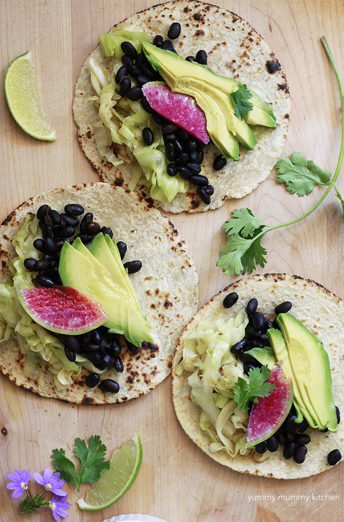Vegan tacos with black beans, cabbage, avocado, and watermelon radish.