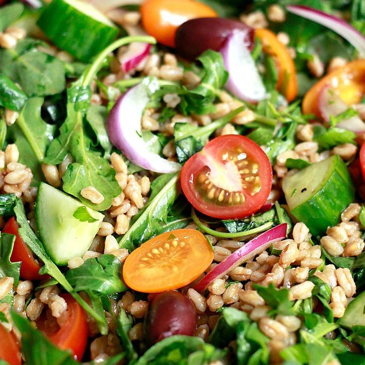 Italian farro salad with arugula, tomatoes, olives, and cucumber.