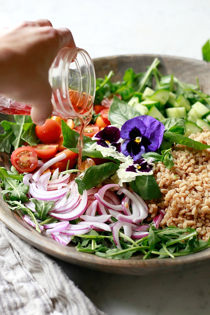 A big bowl of farro salad being dressed with a light red wine vinaigrette.