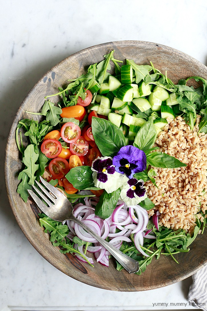 Bowl of Italian farro salad topped with edible flowers and basil.