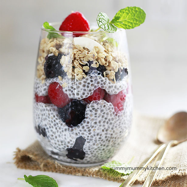 Chia pudding made with almond milk, chia seeds, and fresh berries layered in a glass with granola and mint.