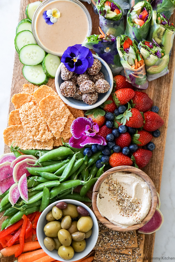 A beautiful vegetarian party platter snack board with fresh homemade vegan spring rolls, hummus and vegetables, olives, crackers, berries, and truffles.