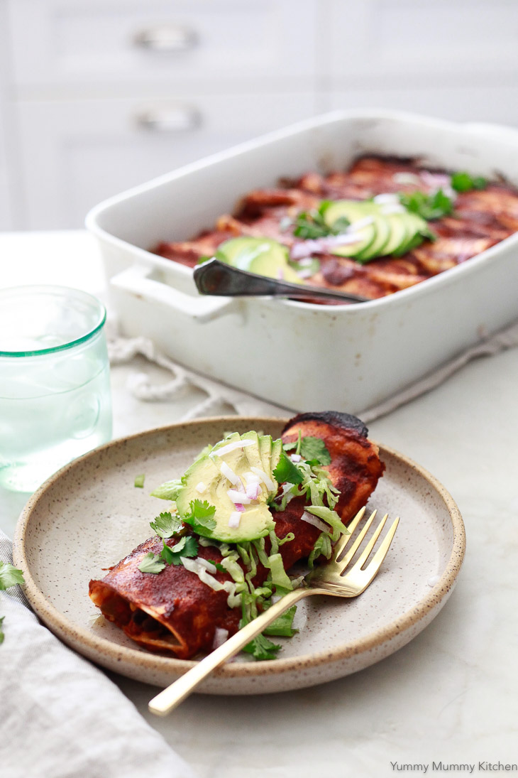 Vegetarian enchiladas in a white kitchen. These delicious enchiladas are filled with black beans and corn.