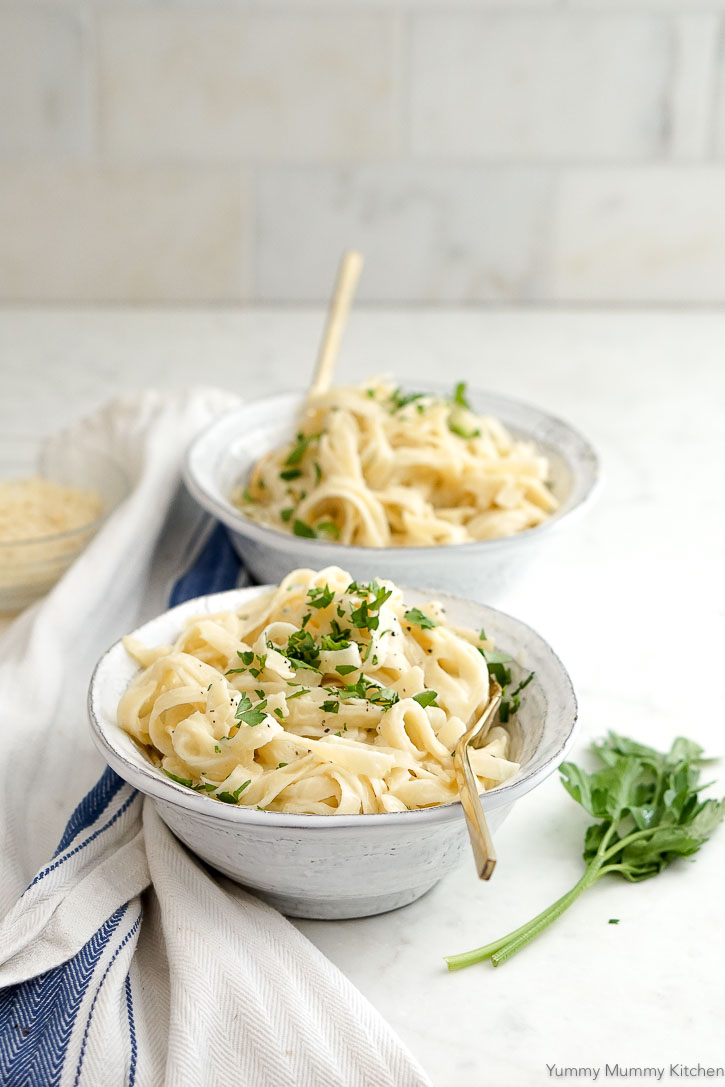 Bowls of delicious creamy vegan cauliflower fettuccini Alfredo topped with parsley.