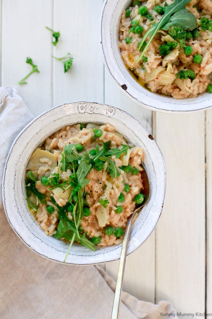 These two lovely bowls of creamy risotto with peas and artichokes were made in the instant pot pressure cooker. They are topped with arugula and herbs. This easy risotto is vegan and gluten free.