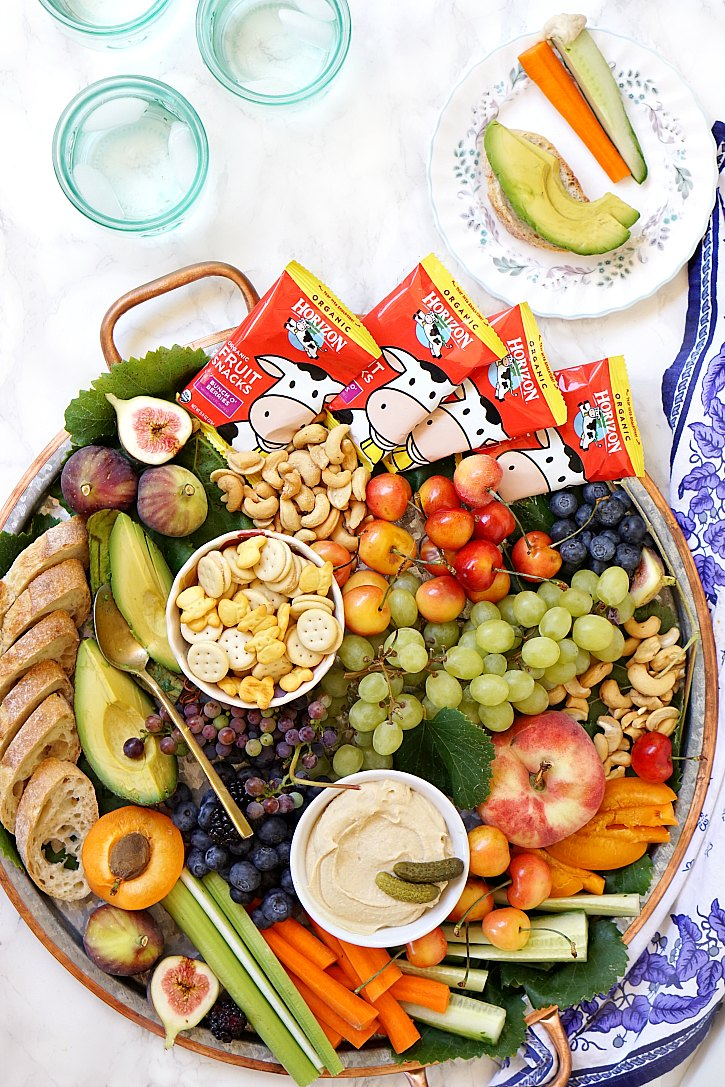 A big kid-friendly snack platter filled with fruit, veggies, hummus, crackers, nuts, and Horizon fruit snacks is perfect for any family party.
