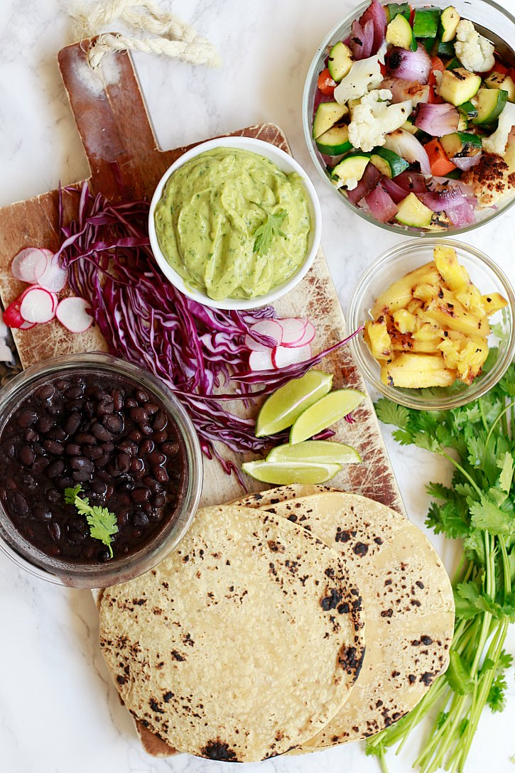 A colorful spread of veggie tacos with black beans, avocado cream sauce, and pineapple.
