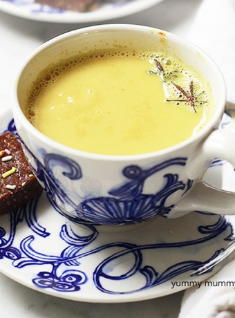 A blue tea cup filled with turmeric tea latte.