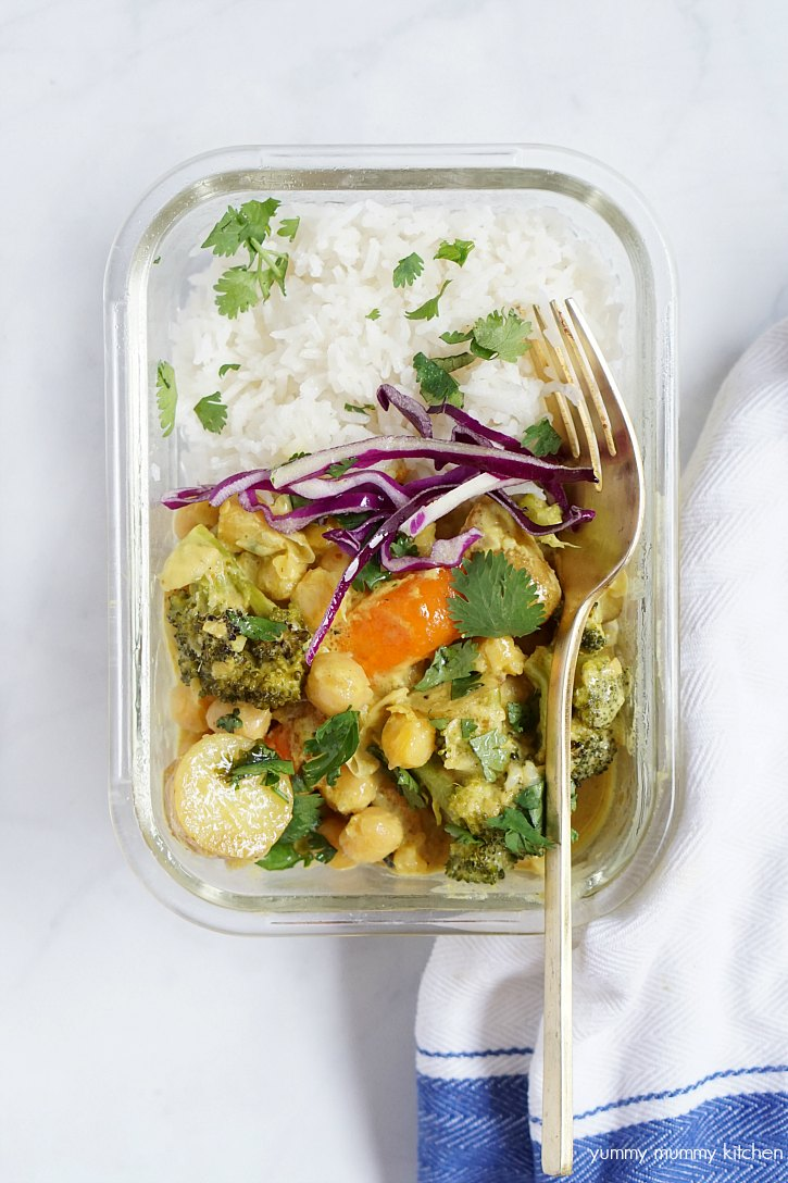 A glass meal prep container with rice and a yellow chickpea curry.