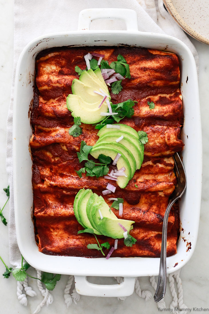 A beautiful pan of red enchiladas topped with sliced avocado, cilantro, and red onion. These delicious black bean enchiladas are vegetarian and vegan friendly.