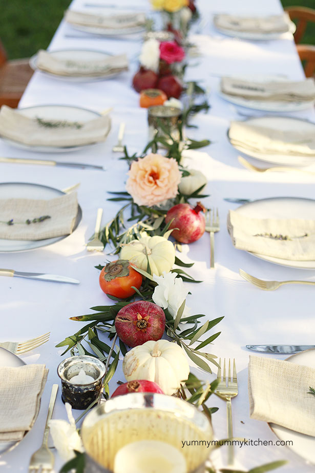 A beautiful dinner party table setting with olive branches, pumpkins, and pomegranates. Perfect for a Thanksgiving table.