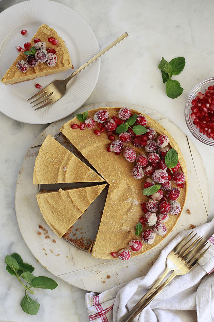 A beautiful vegan pumpkin cheesecake topped with sugared cranberries and fresh mint.
