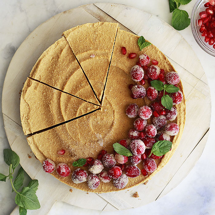 A pretty vegan pumpkin cheesecake gets cut into slices.